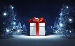 Wrapped gift box in winter glittering magic woods Royalty Free Stock Photography