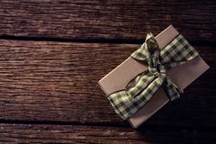 Wrapped gift box on wooden plank Royalty Free Stock Images