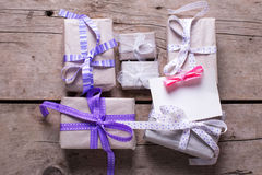 Wrapped  gift boxes with presents  and empty tag on aged wooden Royalty Free Stock Photos