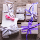 Wrapped  gift boxes with presents  and empty tag on aged wooden Stock Photos