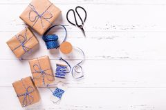 Wrapped  gift boxes with presents, scissors,  blue ribbon  and t. Ags on textured wooden background. Selective focus. Place for text. Flat lay Stock Photo