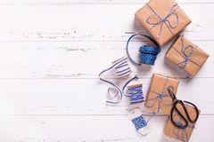 Wrapped  gift boxes with presents, scissors,  blue ribbon  and t. Ags on textured wooden background. Selective focus. Place for text. Flat lay Stock Photos