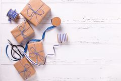 Wrapped  gift boxes with presents,. Scissors,  blue ribbon  and tags on textured wooden background. Selective focus. Place for text. Flat lay Stock Photography