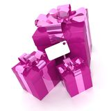 Wrapped gift boxes with tag. Wrapped pink and lilac gift boxes with ribbons, bows and blank, label, white background Stock Photo