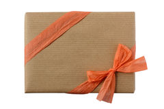 Wrapped gift  in brown kraft paper decorated with peach orange ribbon Royalty Free Stock Photo