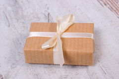 Wrapped gift for Christmas or other celebration on old wooden background Stock Photo