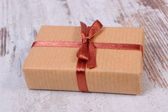 Wrapped gift for Christmas or other celebration on old wooden background Stock Image