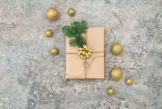 Wrapped gift golden Christmas decoration Flat lay. Wrapped gift and golden Christmas decoration on grey background. Flat lay royalty free stock image
