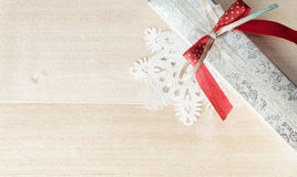 Wrapped gift and paper snowflakes on wood. Christmas siver red b Royalty Free Stock Photography