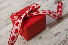 Wrapped gift with red ribbon, decoration for Valentines Day. Wrapped gift with red ribbon on old rustic wooden background, decoration for Valentines Day Royalty Free Stock Photography
