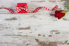 Wrapped gift with red ribbon and rose for Valentines Day, copy space for text. Wrapped gift with red ribbon and rose on old wooden background, decoration for Stock Images