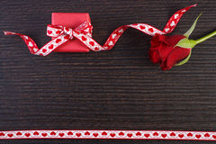 Wrapped gift with red ribbon and rose for Valentines Day, copy space for text. Wrapped gift with red ribbon and rose on wooden background, decoration for Stock Photography