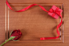 Wrapped gift with red ribbon and rose for Valentines Day, copy space for text. Wrapped gift with red ribbon and rose on wooden background, decoration for Royalty Free Stock Images