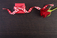 Wrapped gift with red ribbon and rose for Valentines Day, copy space for text. Wrapped gift with red ribbon and rose on wooden background, decoration for Royalty Free Stock Photography