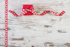 Wrapped gift with red ribbon for Valentines Day, copy space for text. Wrapped gift with red ribbon on old wooden background, decoration for Valentines Day, copy Stock Photo