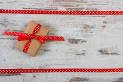 Wrapped gift with red ribbon for Valentines Day, copy space for text. Wrapped gift with red ribbon on old wooden background, decoration for Valentines Day, copy Royalty Free Stock Photo
