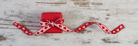 Wrapped gift with red ribbon for Valentines Day. Wrapped gift with red ribbon on old wooden background, decoration for Valentines Day Stock Images