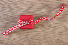Wrapped gift with red ribbon for Valentines Day. Wrapped gift with red ribbon on wooden background, decoration for Valentines Day Royalty Free Stock Photo