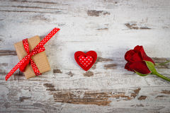 Wrapped gift with ribbon, red heart and rose for Valentines Day Stock Photo