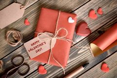 Wrapped gift tied up with cord, cardboard tag with text. `Happy Valentine` and wrapping materials on wooden table. Valentines concept stock photo