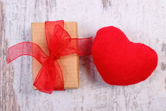 Wrapped gift for Valentines day and red heart on old wooden plank Stock Photo