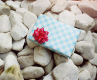Wrapped gift on the white rock Stock Photography