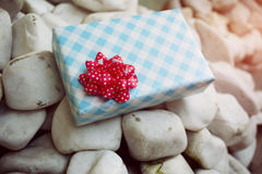 Wrapped gift on the white rock Stock Images