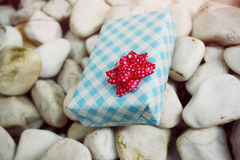 Wrapped gift on the white rock Royalty Free Stock Photos