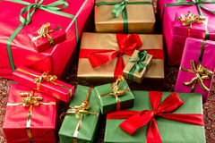 Wrapped Gifts Assorted by Color. Bulk of plain presents grouped in red, gold, green and magenta. Shallow depth of field. Focus on front third. Background for any Royalty Free Stock Image