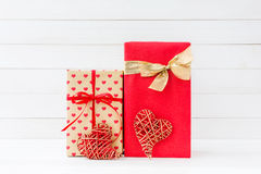 Wrapped gifts boxes and two red hearts on white wooden backgroun Stock Photography