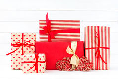 Wrapped gifts boxes and two red hearts on white wooden backgroun Stock Image
