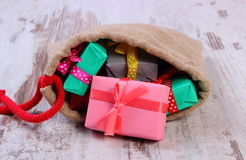 Wrapped gifts in jute bag for Christmas or other celebration Stock Photos
