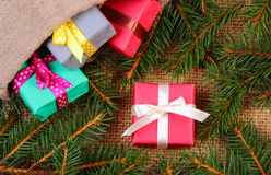 Wrapped gifts in jute bag for Christmas or other celebration and spruce branches Royalty Free Stock Photos