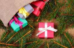 Wrapped gifts in jute bag for Christmas or other celebration and spruce branches Royalty Free Stock Image