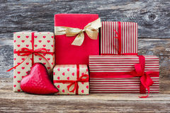 Wrapped gifts and red heart on wooden background. Toned, soft focus, vintage style Stock Photography