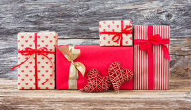 Wrapped gifts and two red hearts on wooden background. Toned, soft focus, vintage style Royalty Free Stock Photos