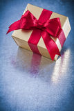 Wrapped golden giftbox with red ribbon bow top view Stock Images