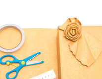 Wrapped golden present box with  wrapping tools nearby Stock Images