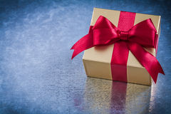 Wrapped golden present with red ribbon bow horizontal view Royalty Free Stock Photography