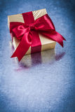 Wrapped golden present with red ribbon bow top view Royalty Free Stock Image