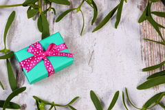 Wrapped green gift for Christmas and frame of mistletoe on old wooden background Stock Image