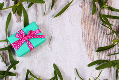 Wrapped green gift for Christmas and frame of mistletoe on old wooden background Royalty Free Stock Photography