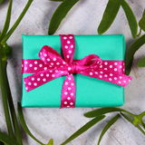 Wrapped green gift for Christmas and mistletoe on old wooden background Royalty Free Stock Photos