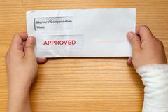 Wrapped hand holding envelope with workers compensation claim and result of approved removeable words with clipping path. Wrapped hand holding an envelope with royalty free stock images