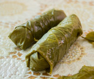 Wrapped meat in green vine leaves a decorated board Stock Photo