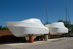 Wrapped motor boats. Two motor boats wrapped, packaged, in white plastic material and standing on supports against a red brick wall Royalty Free Stock Photography