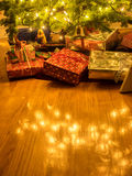 Wrapped packages under Christmas tree. Colorful gift wrapped packages stacked under a Christmas tree with the white tree lights reflected on a hardwood floor Royalty Free Stock Images
