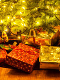 Wrapped packages under Christmas tree. Colorful gift wrapped packages stacked under a Christmas tree with the white tree lights reflected on a hardwood floor Royalty Free Stock Photo