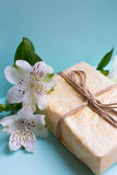 Wrapped parcel with alstroemeria flowers on mint background Royalty Free Stock Images