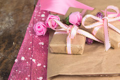 Wrapped in parchment paper, delicate fresh pink flowers with golden heart Stock Photos